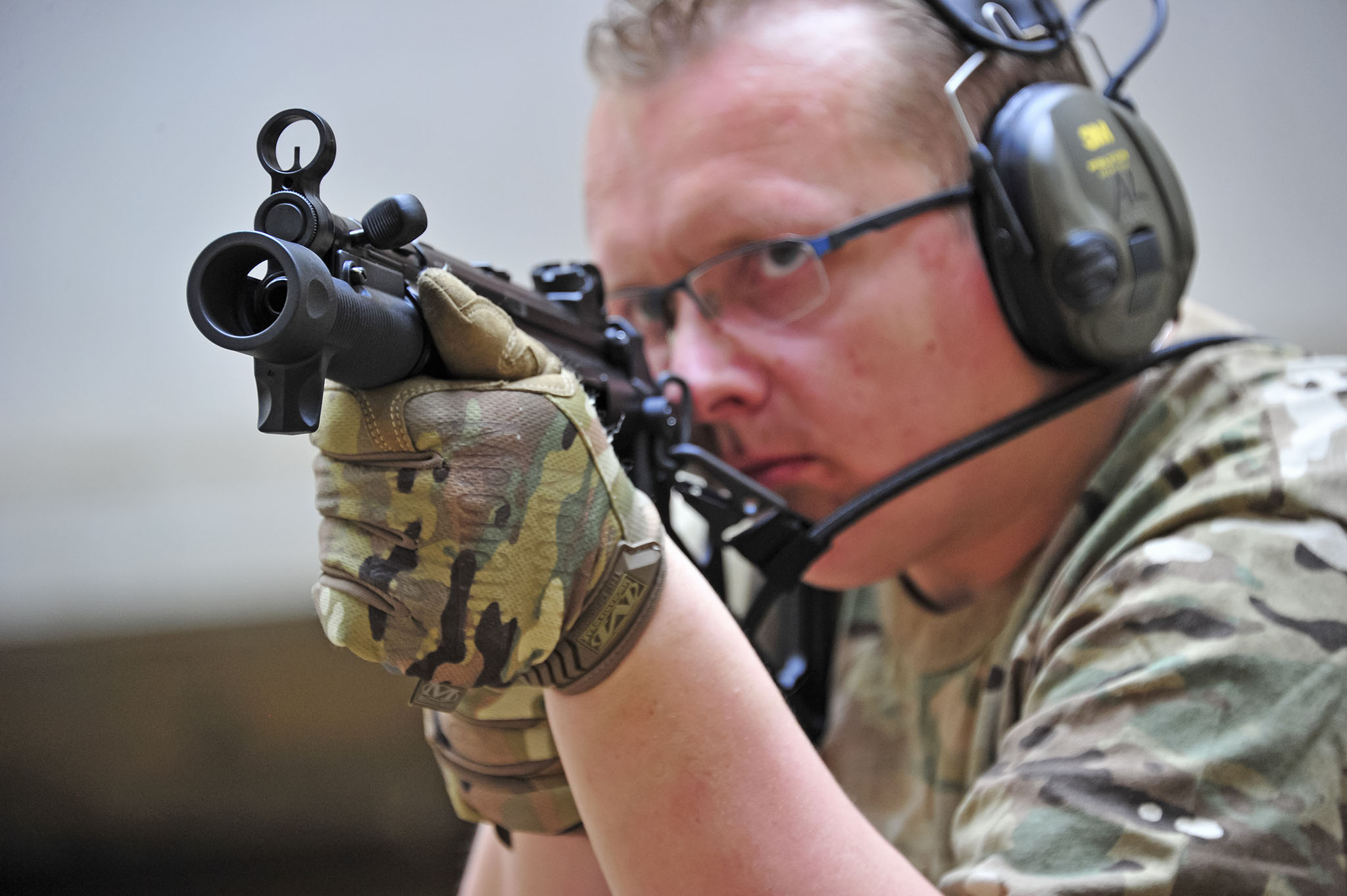 Shooter holding a stocked Heckler & Koch SP5K pistol