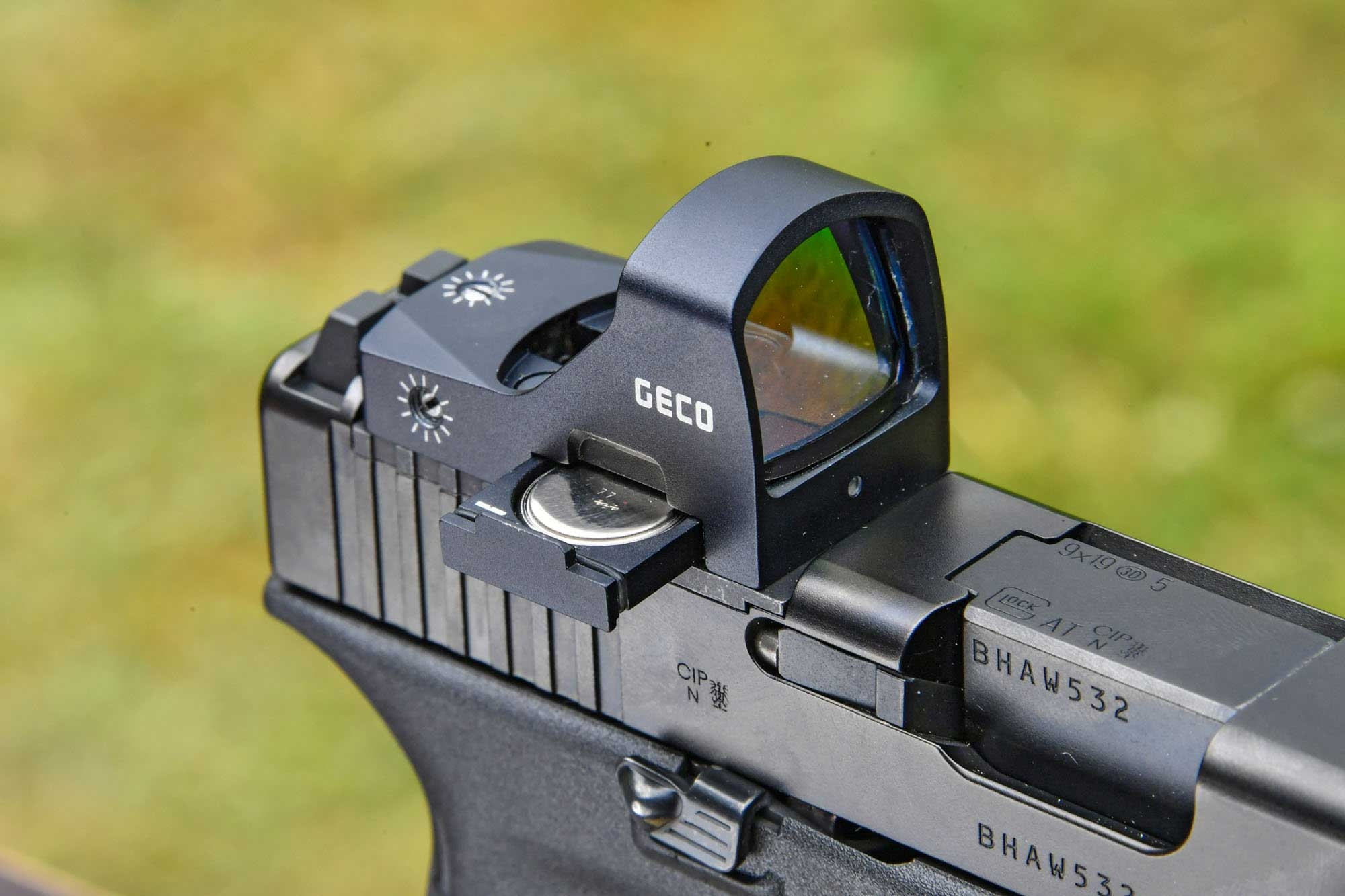 Herausgeschobenes Batteriefach des GECO Open Red Dot Sights.