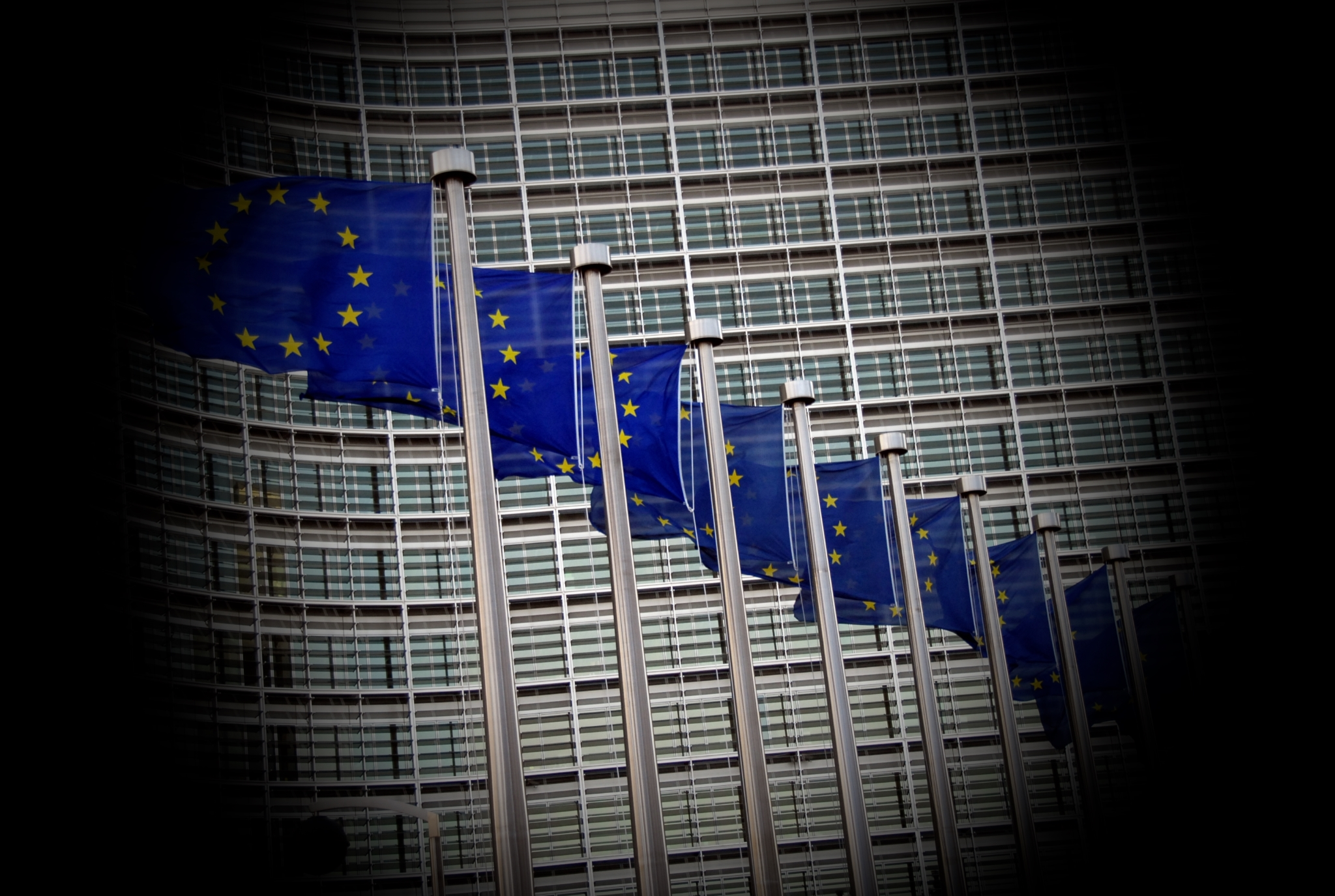 EU flags in front of the European Commission building, with black borders