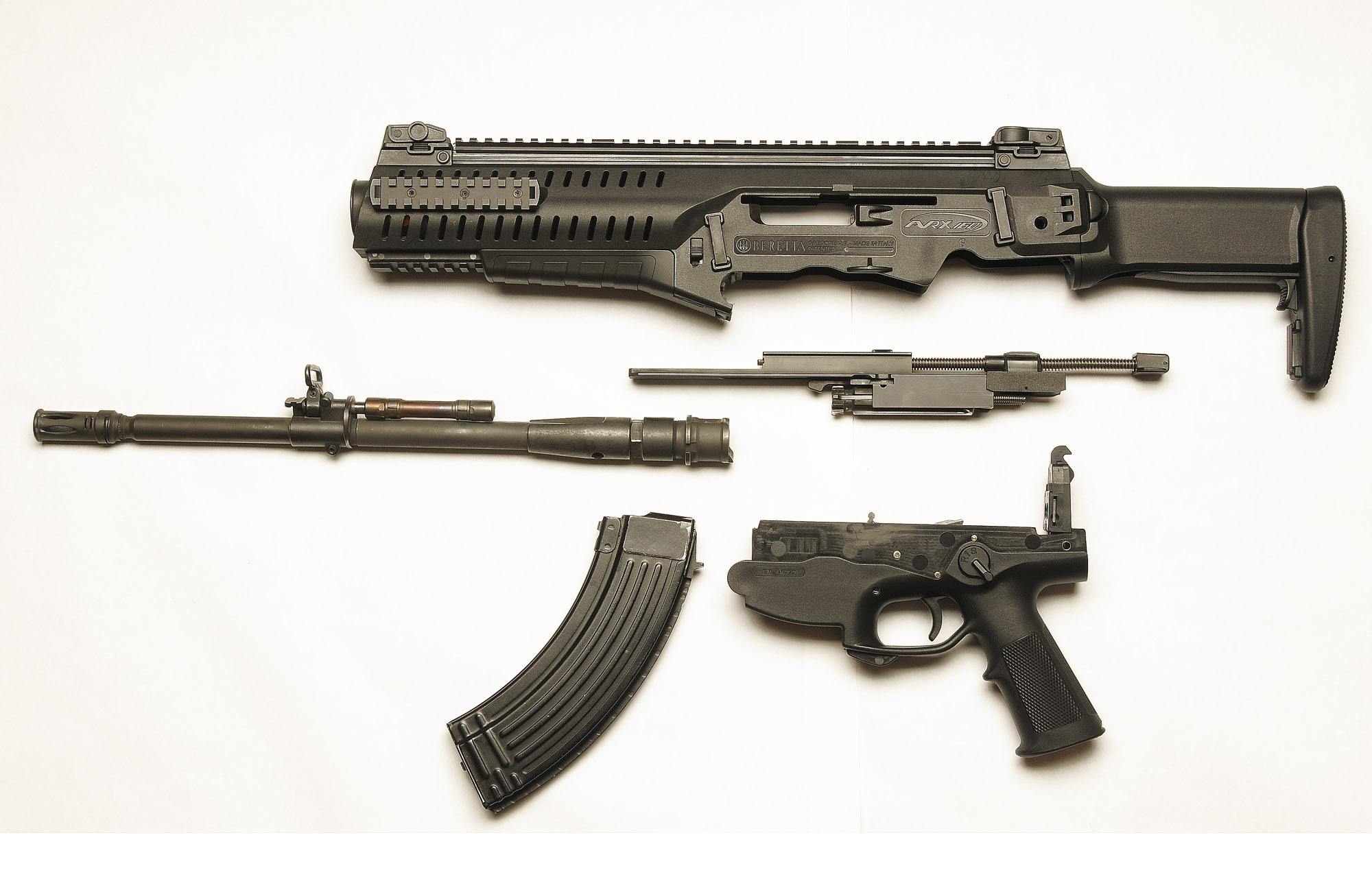 The Soviet 7.62 caliber ARX-160, field disassembled. The three main subassemblies for the conversion in the Soviet chambering are barrel, magazine well and bolt carrier assembly. Plus, of course, an AK/AKM magazine...