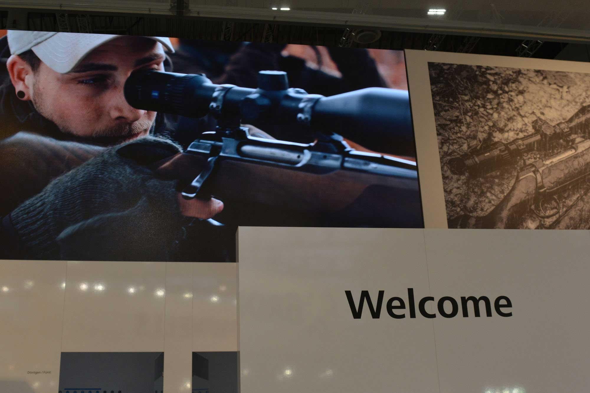 Huge image of a hunter with rifle looking through a ZEISS riflescope.