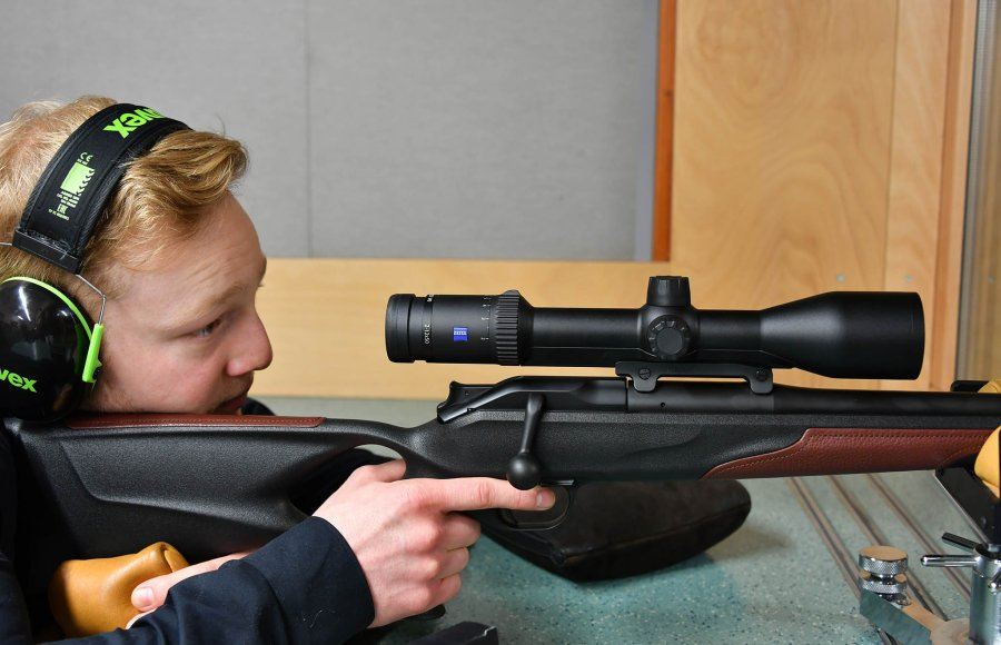 Shooter with hearing protection looks through ZEISS Conquest V6