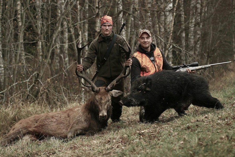 Hunters on a successful hunt with red stag and wild boar
