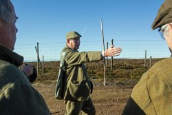 A gamekeeper with clients on driven grouse day