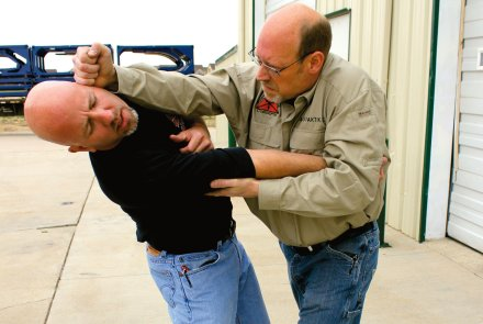 The victim controls the elbow of his attacker for self-defense.