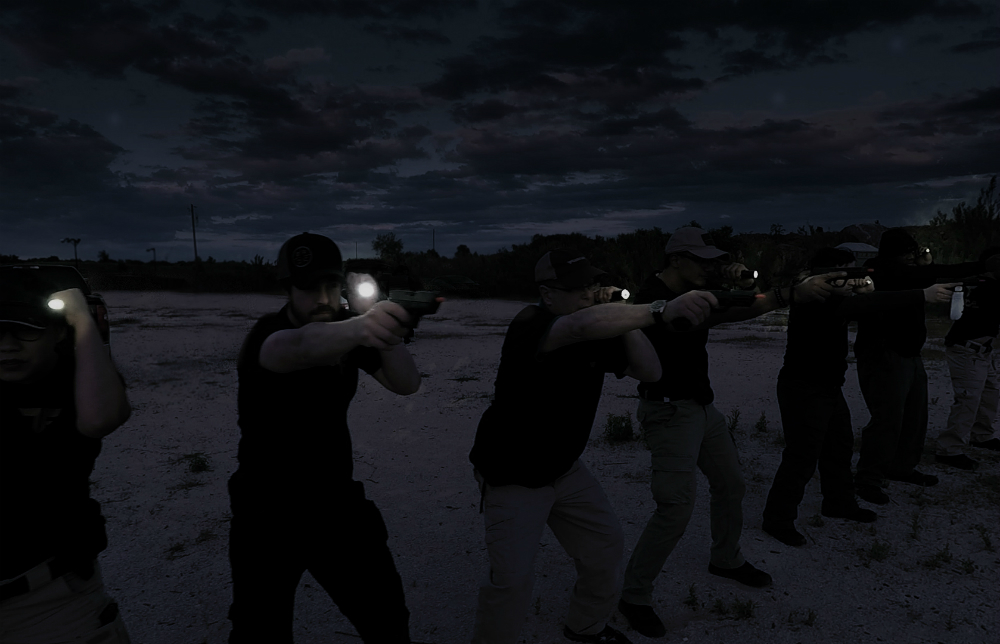 Men shooting in the dark with flashlights