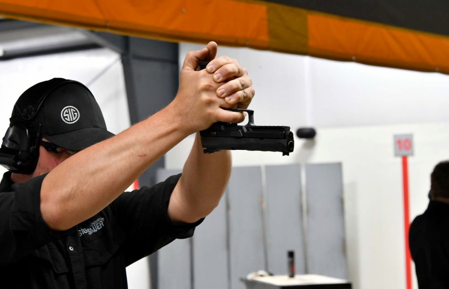 Professional instructor of the SIG Sauer Academy showing how to fire an handgun upside down.