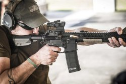 Shooter shooting with an automatic rifle with Trijicon ACOG 1-5x16 mounted on it.