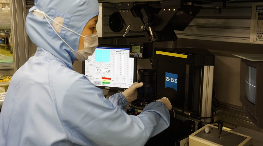 A Zeiss worker operating an optics quality control machinery