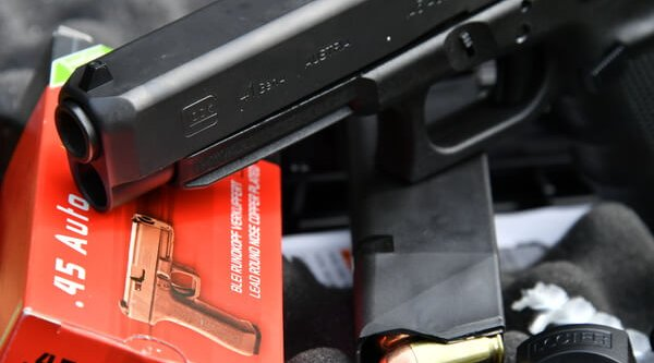 The muzzle and barrel section of the GLOCK 41 MOS polymer pistol, with the magazine and ammo