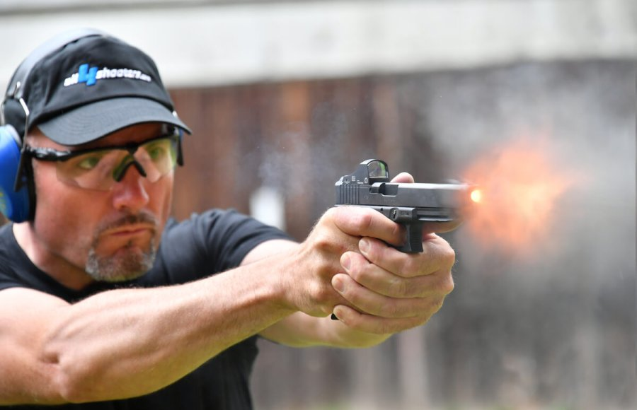 Sports shooter firing a GLOCK pistol from the MOS series