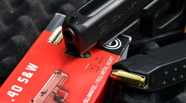 The muzzle and barrel section of the GLOCK 35 MOS polymer pistol, next to the magazine and ammo.