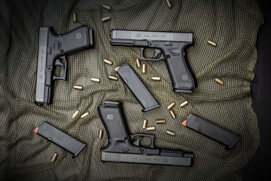 GLOCK pistols G17, G19 and G34 Gen5 MOS lie next to clips and bullet cases in 9 mm Luger on a net.