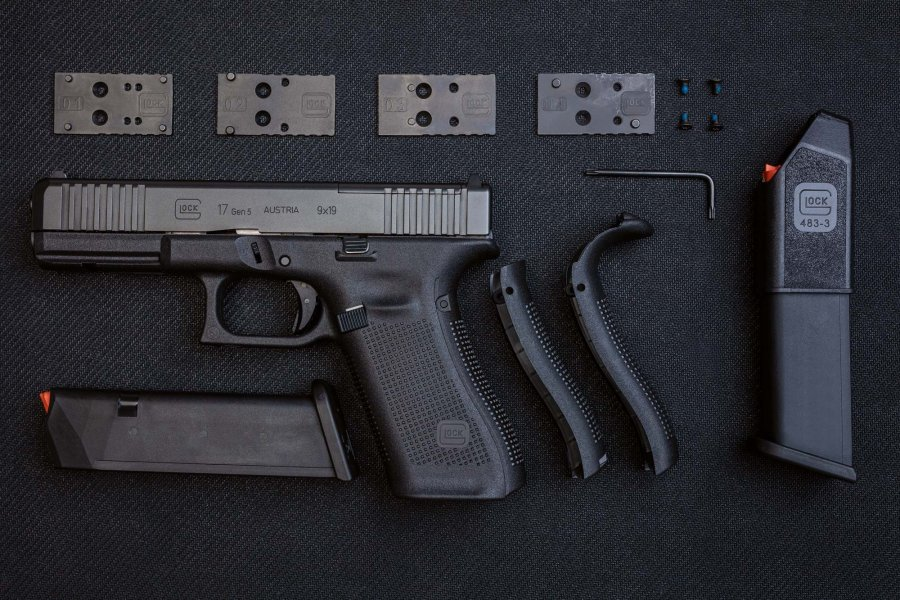 The new G17 Gen5 MOS with the 4 adapter plates for the mounting of mini spotlight sights, 2 gun magazines, alternative grips and the necessary tools.
