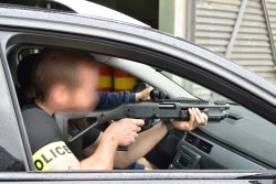 poliziotto in automobile con arma